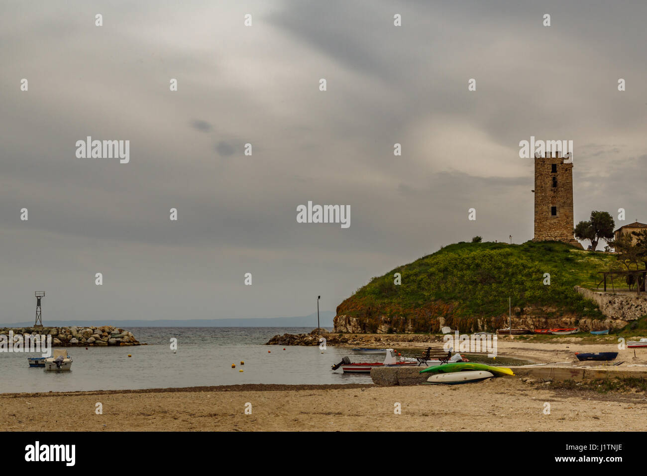 Byzantine tower on a hill by the sea and against a cloudy sky and beach with boats, Nea Fokaia, Greece - Stock Image