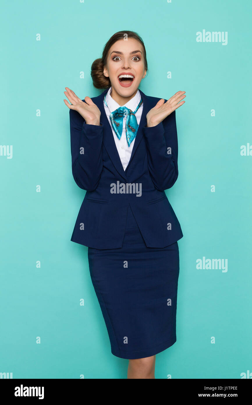Happy young woman in blue suit and turquoise scarf is standing with hands raised and shouting. Three quarter length - Stock Image