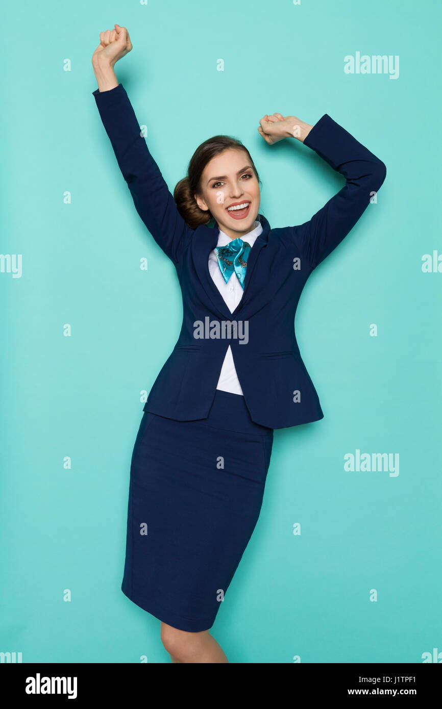 Happy young woman in blue suit and turquoise scarf is standing with arms outstretched and laughing. Three quarter - Stock Image