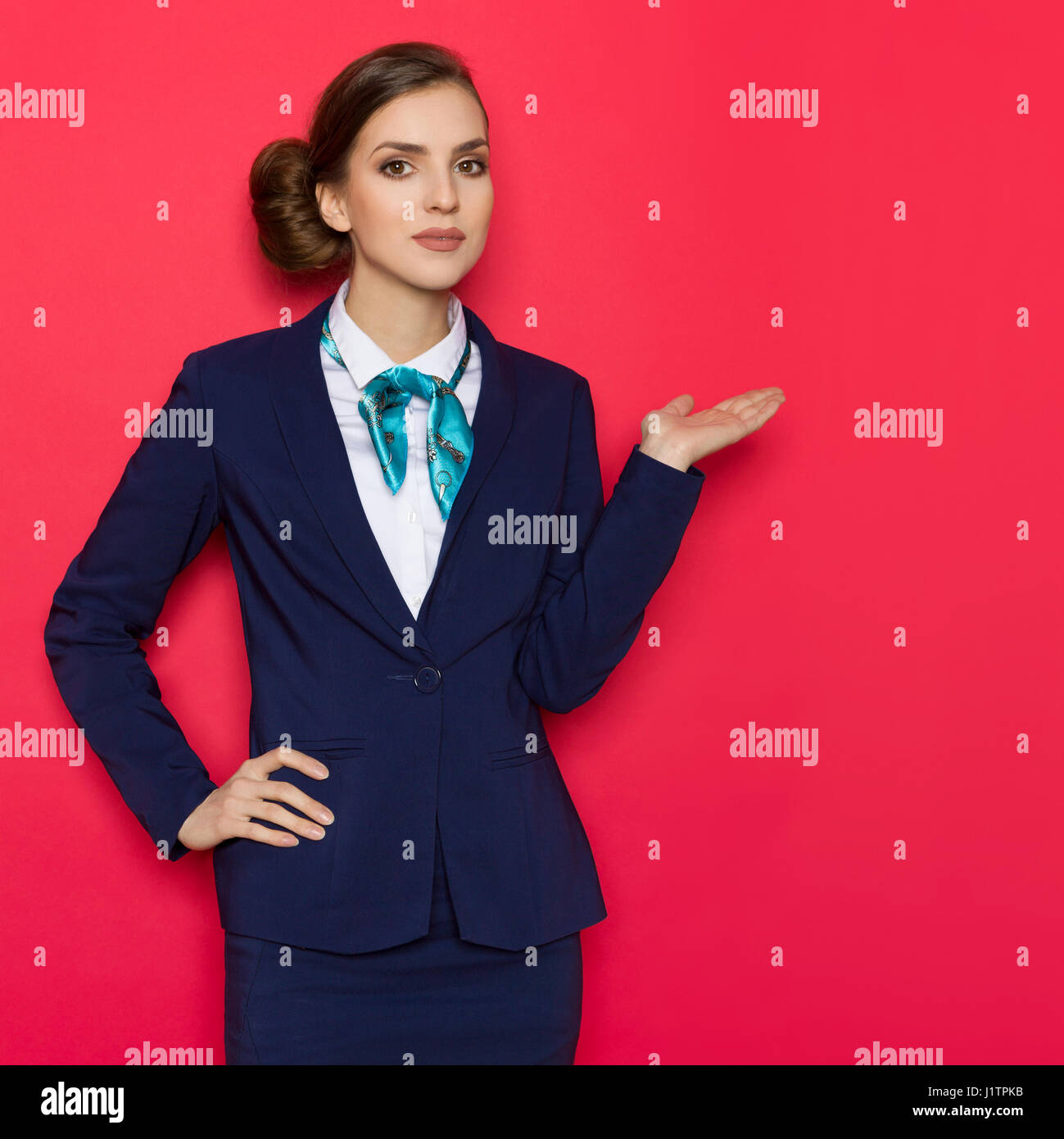 Young woman in blue suit and turquoise scarf is posing with hand raised and presenting something. Three quarter - Stock Image