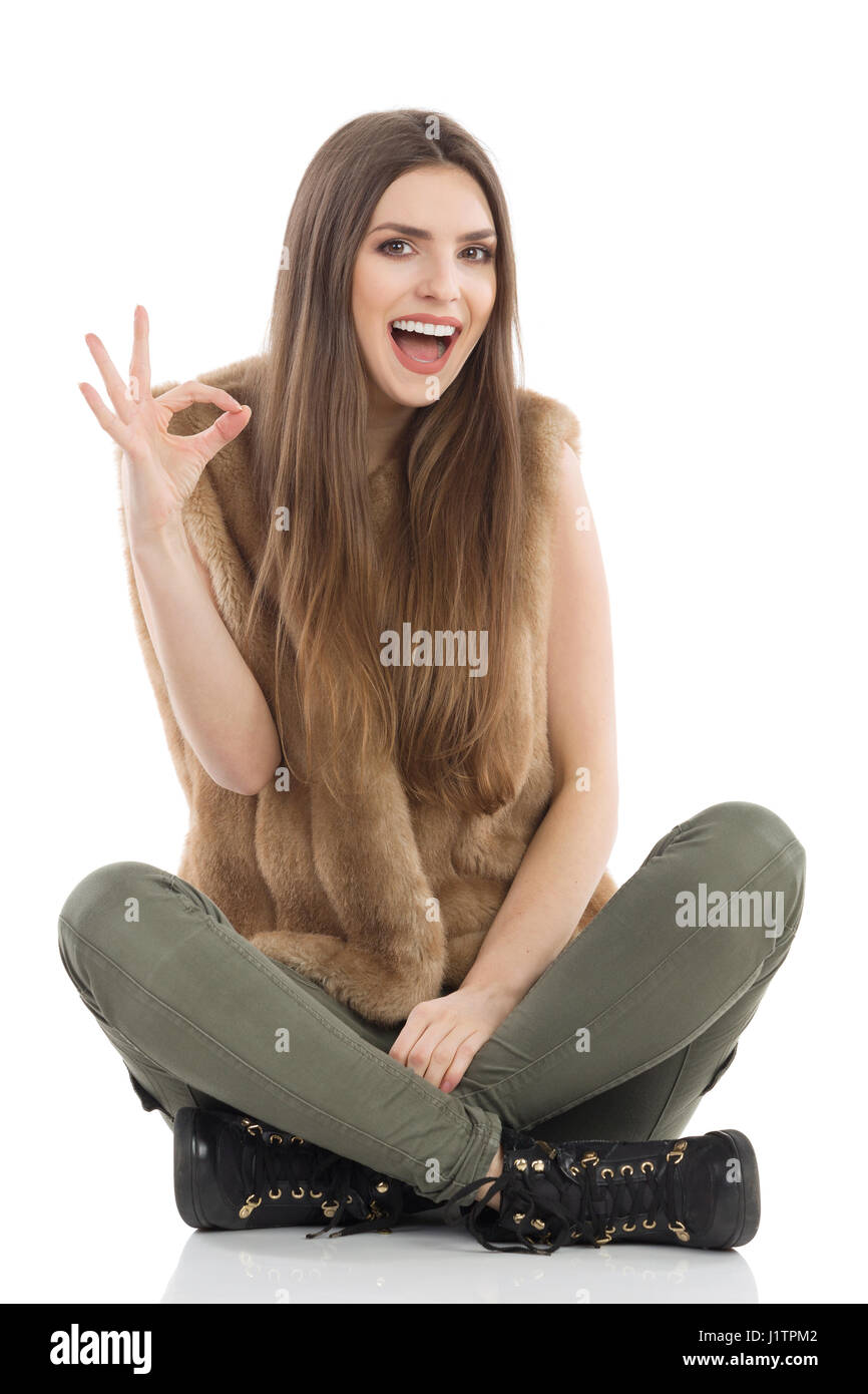 Beautiful young woman in brown fur waistcoat and khaki pants sitting on floor with legs crossed, laughing and showing - Stock Image