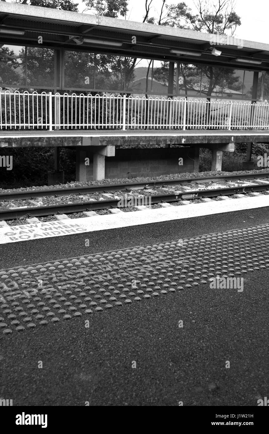 Black and white industrial railway station platform - Stock Image