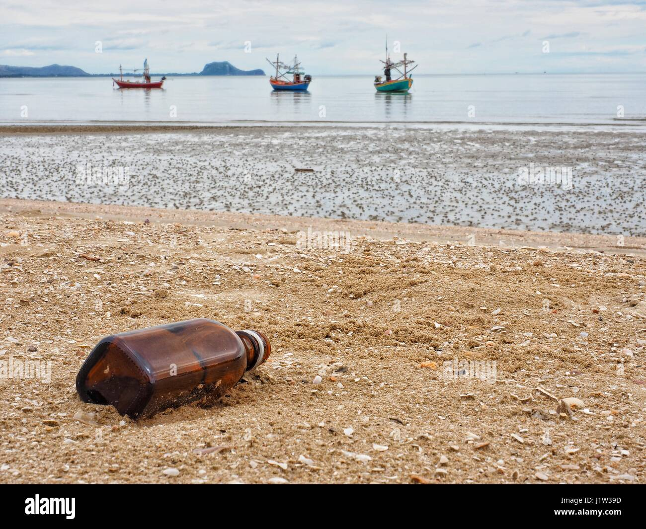 A brown glass bottle thrown away in the beautiful sand beach as garbage, waste on sand, polluted sea, Dolphin Bay, - Stock Image