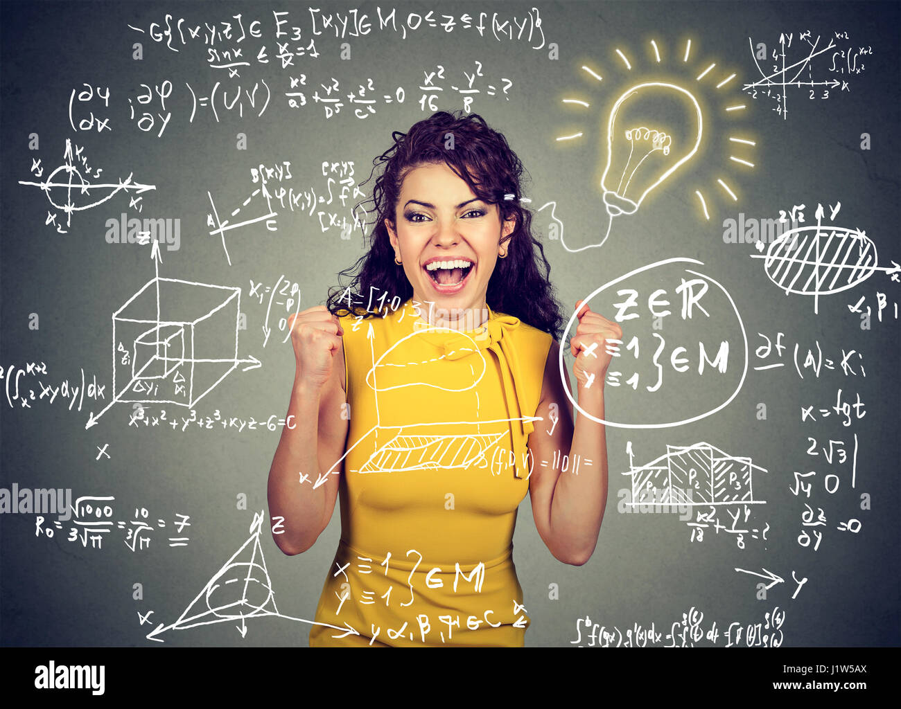smart excited woman student with bright idea light bulb and high school maths and science formulas on blackboard - Stock Image