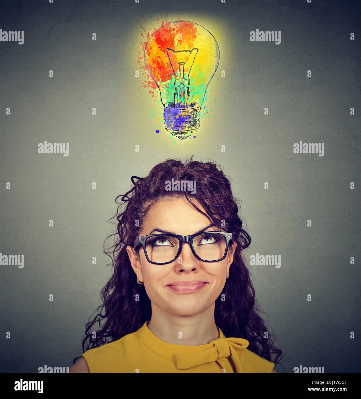 Portrait of a woman with glasses and creative idea looking up at colorful light bulb on gray wall background. Inspiration - Stock Image