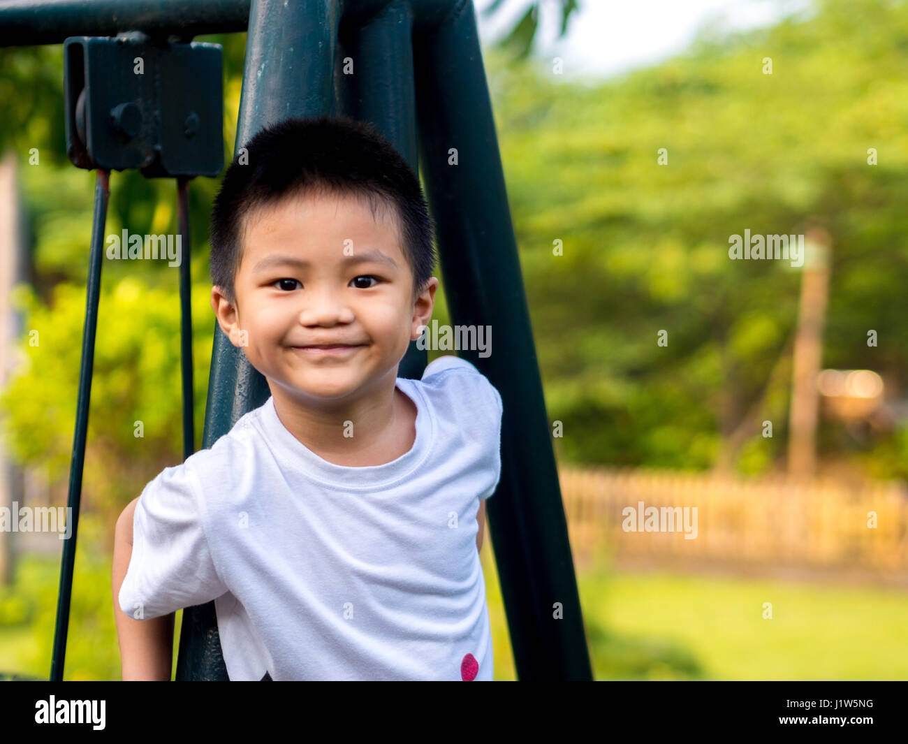 Chinese Child (boy) Climb on The Swings - Stock Image