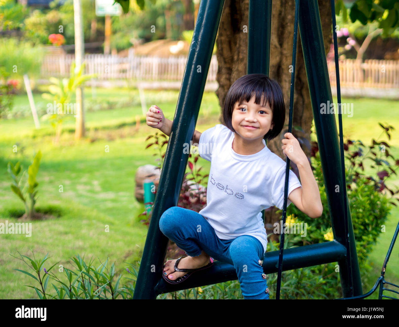 Chinese Child (girl) Climb on The Swings - Stock Image