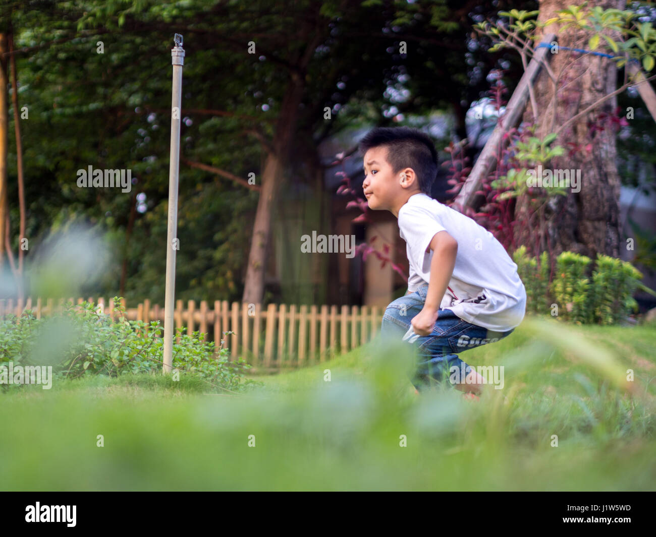 Chinese Child (boy) Crouch on The Park - Stock Image