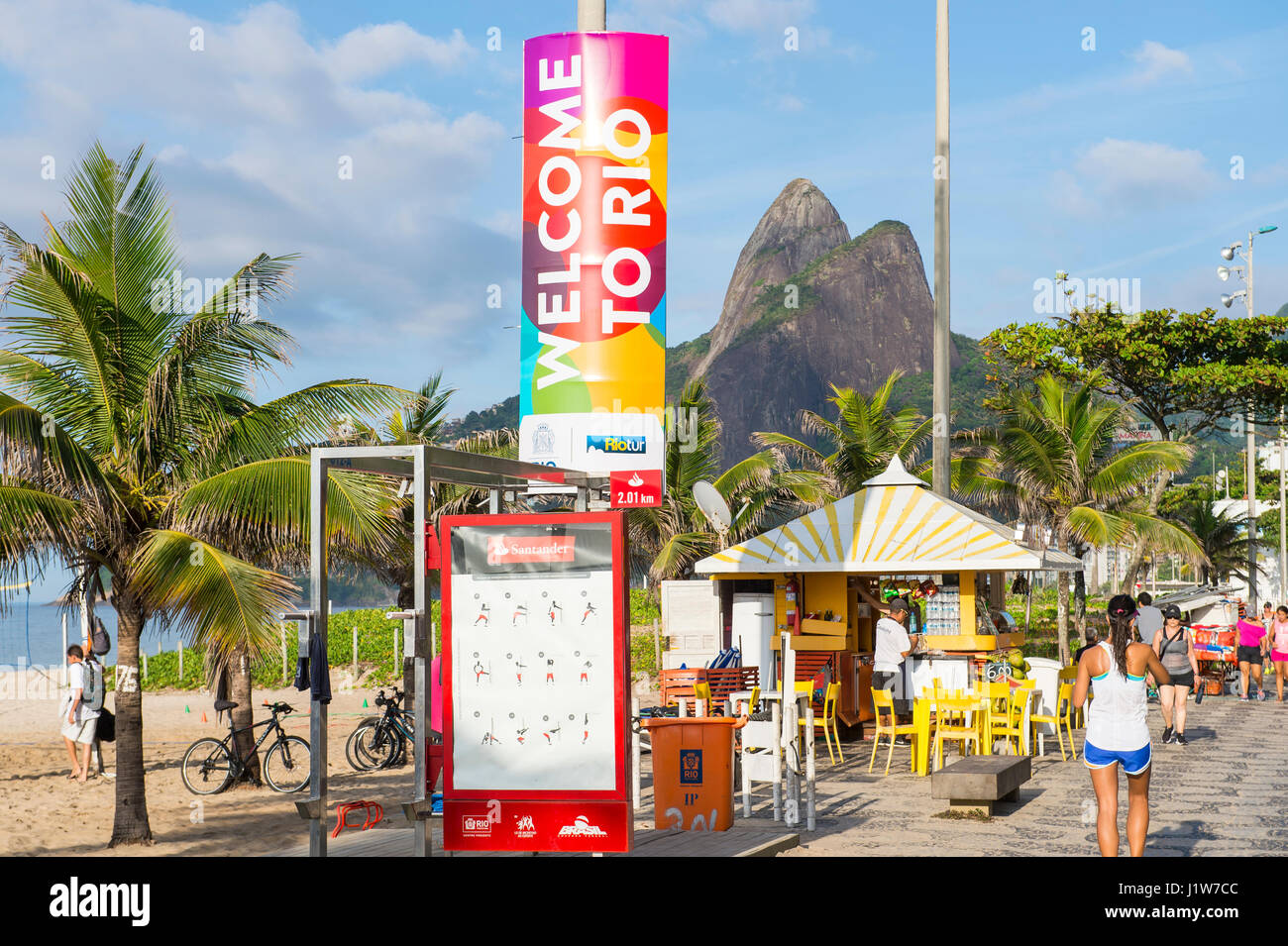 RIO DE JANEIRO - FEBRUARY 21, 2017: Colorful Welcome to Rio sign stands above Ipanema Beach as locals pass on the - Stock Image