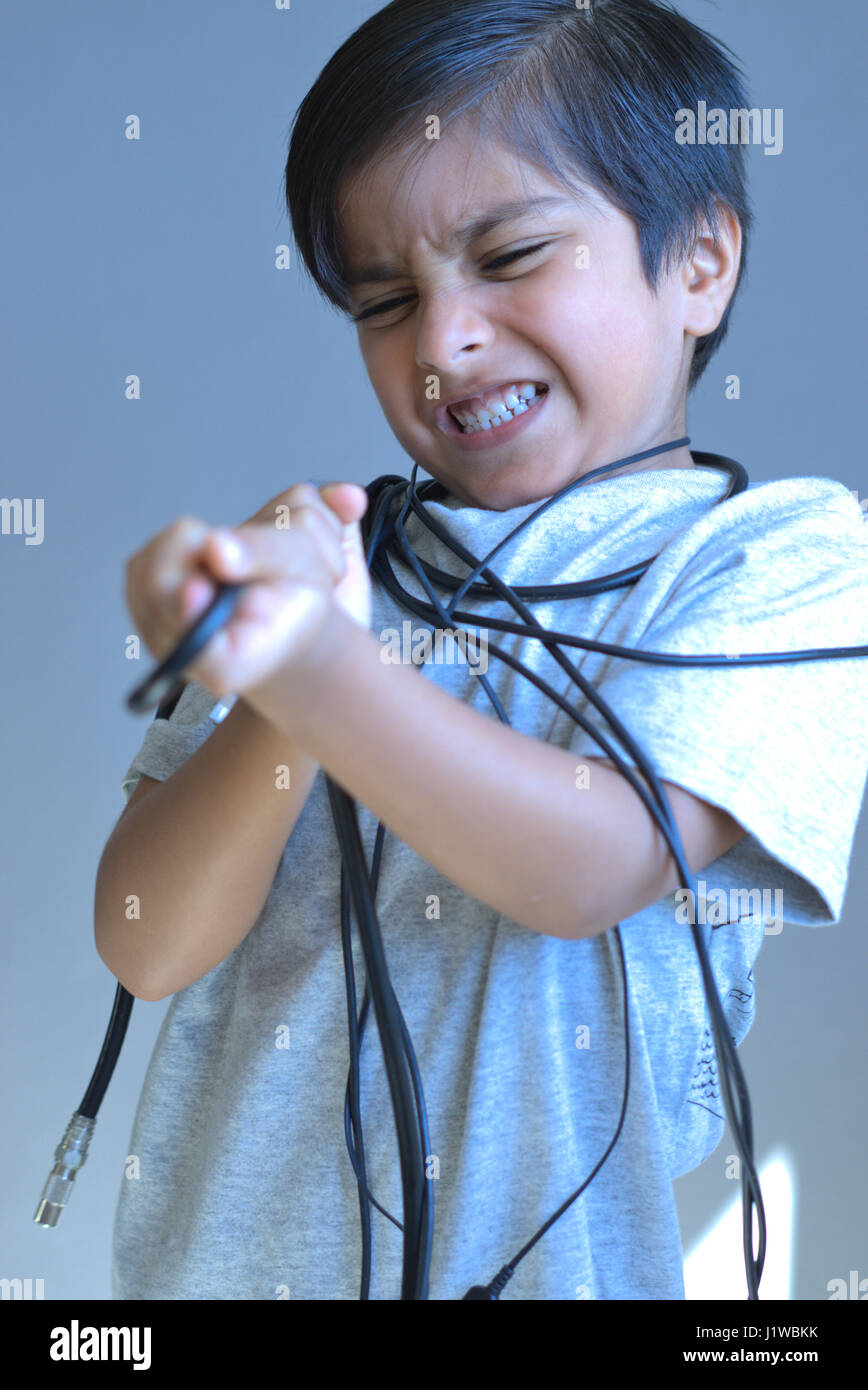 Little Furious kid tangled in wires. Frustrated Kid trying to break free. Unhappy child. - Stock Image