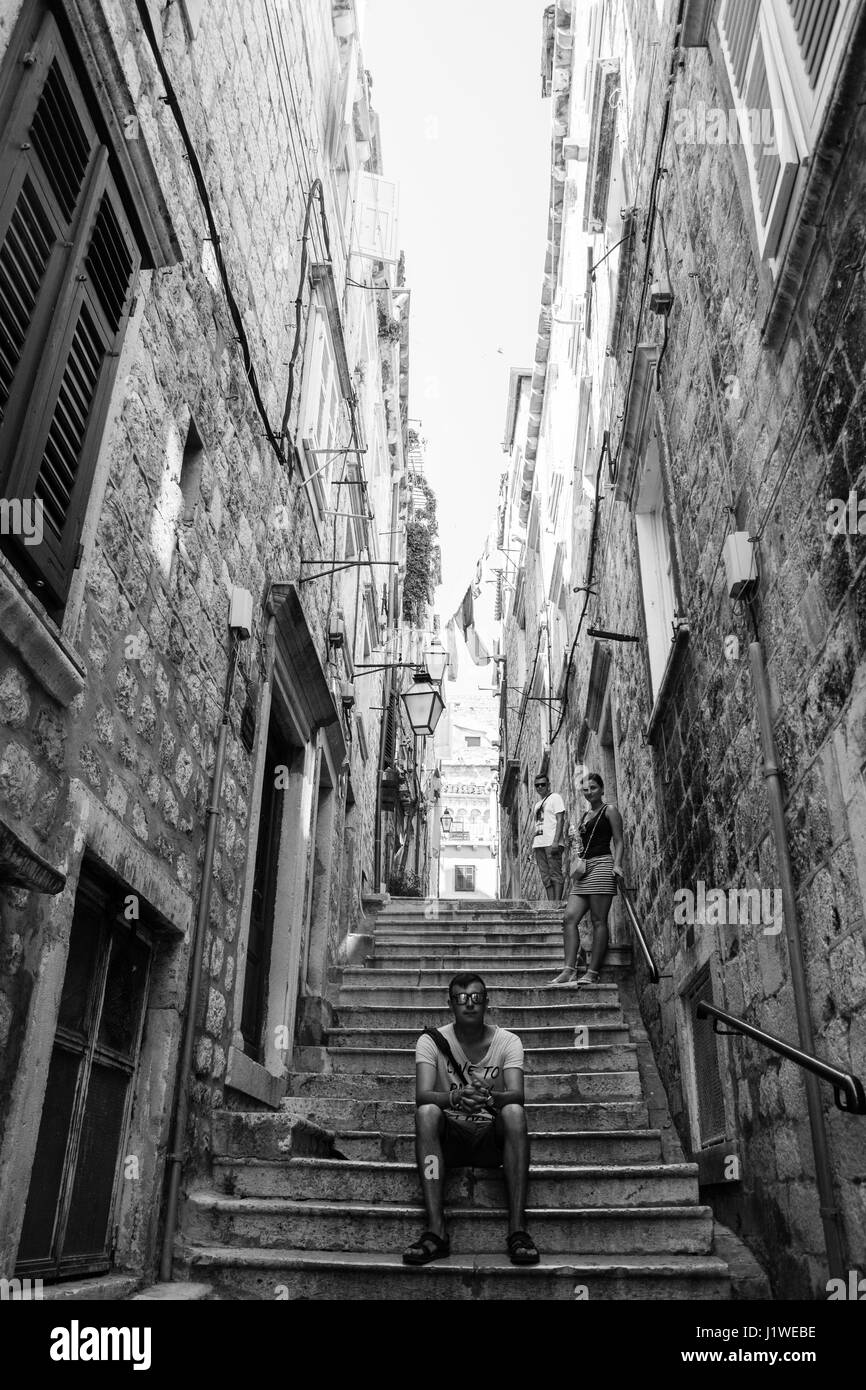 Young Man Sitting on a Steps in old Town - Stock Image