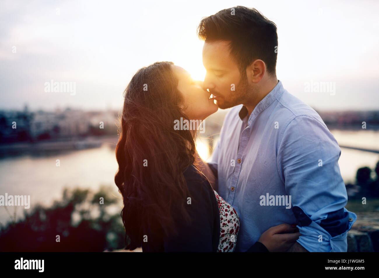 Romantic couple in love cuddling and kissing outdoors during sunset romantic couple in love cuddling and kissing outdoors during sunset altavistaventures Choice Image