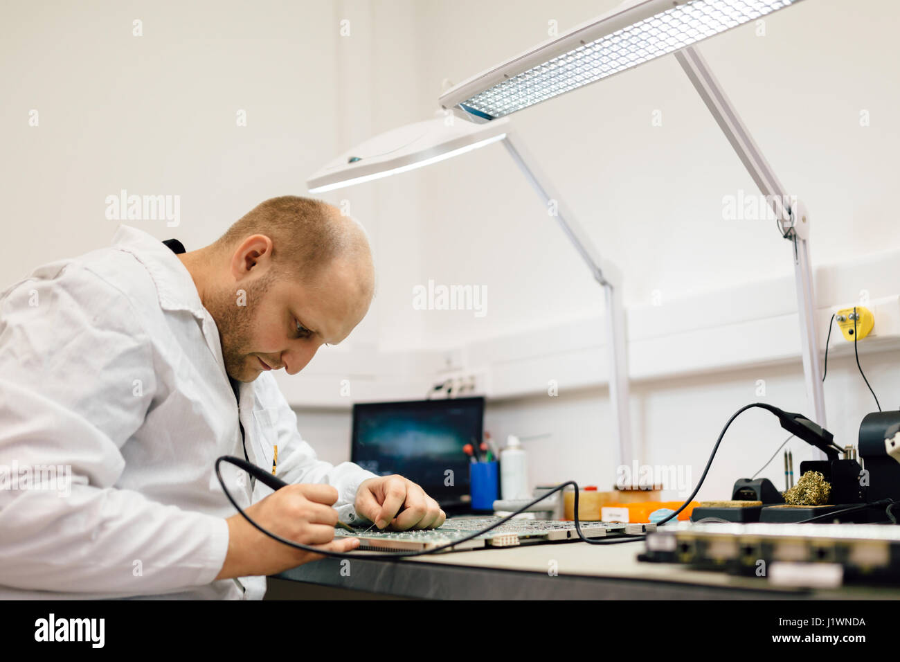 Technician fixing motherboard by soldering chips - Stock Image