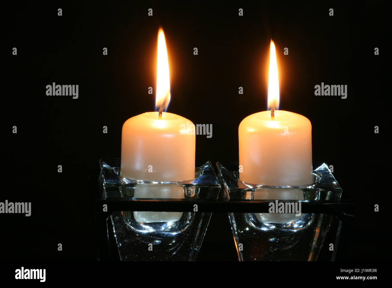 burning candles in glass candlestick - Stock Image