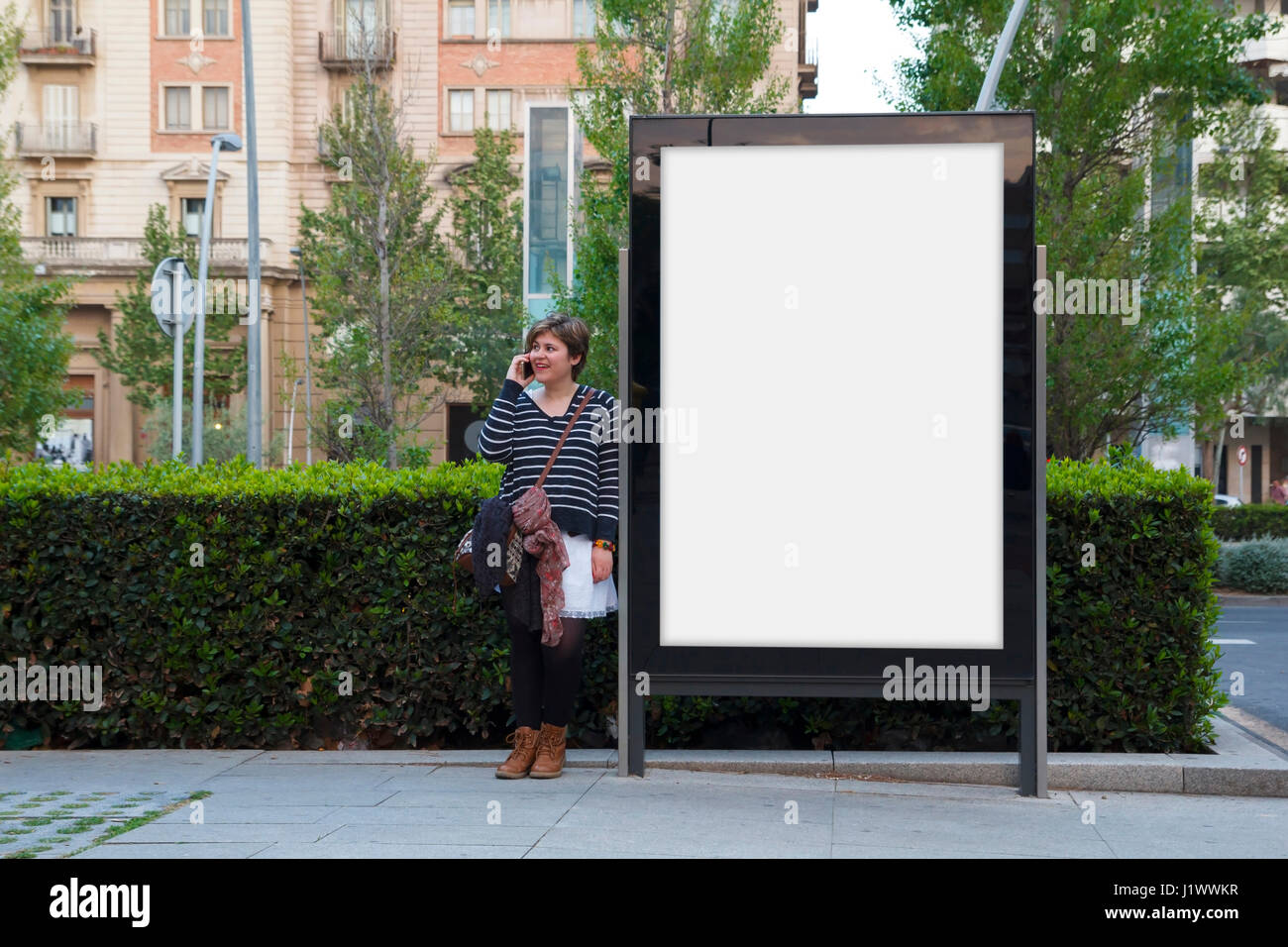 Woman talking with mobile phone, standing in a blank billboard - Stock Image