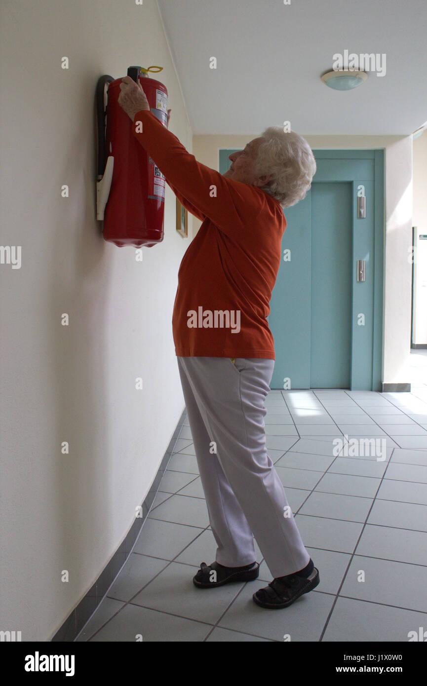 Feuerlöscher zu hoch montiert: im Ernstfall ein Problem für kleine und ältere Hausbewohner; fire - Stock Image