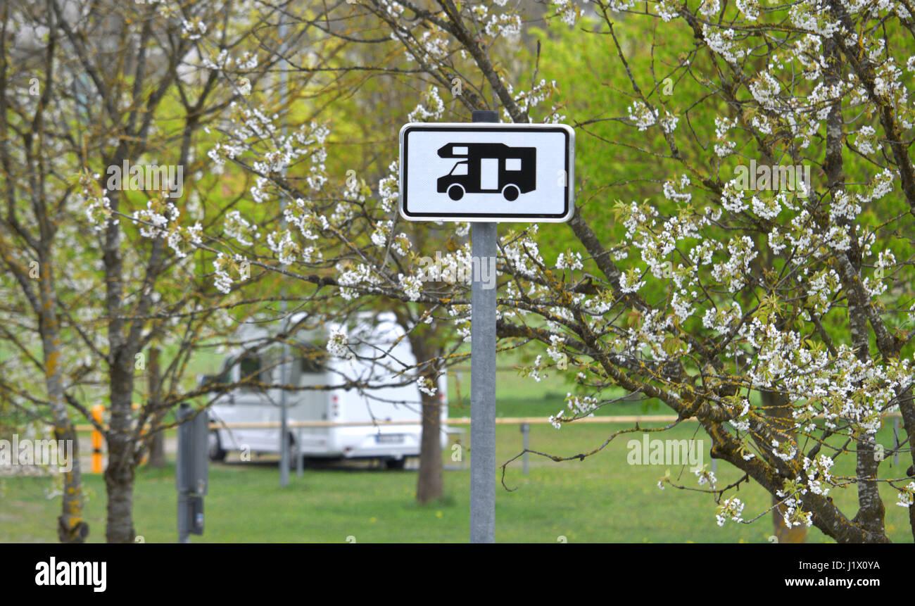 Zeichen, Schild für Wohnmobil-Stellplatz, im Hintergrund hinter blühenden Bäumen ein Reisemobil; - Stock Image