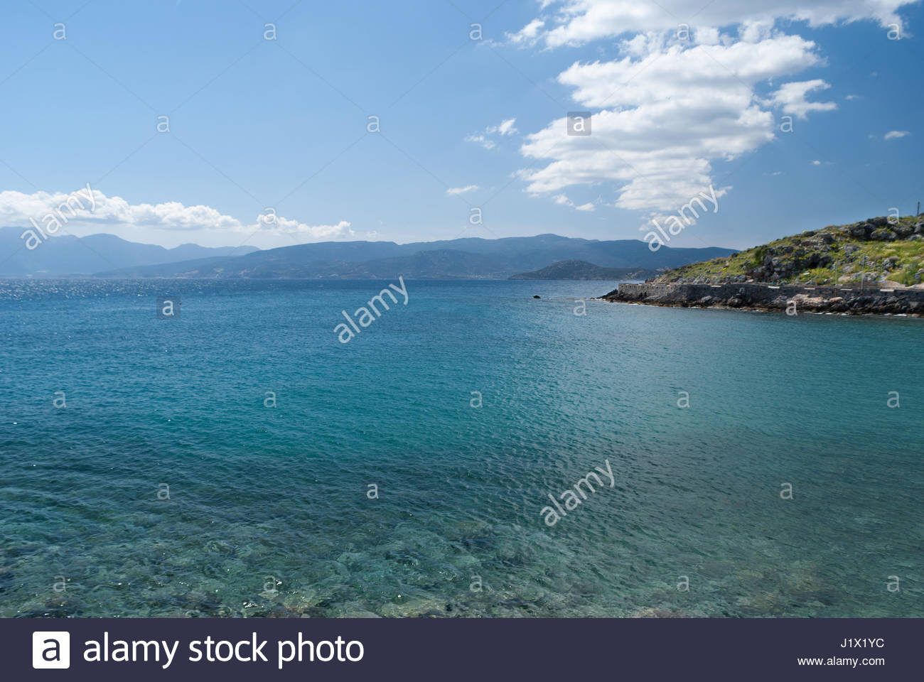 Rock waterfront seacscape & mountains across water Stock Photo