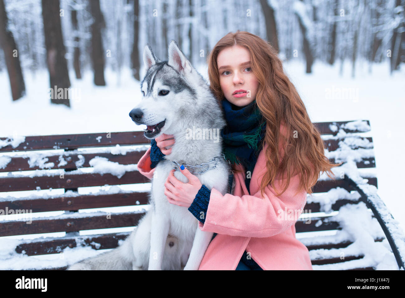 f38d53c012c Beautiful woman sitting on the bench with siberian husky