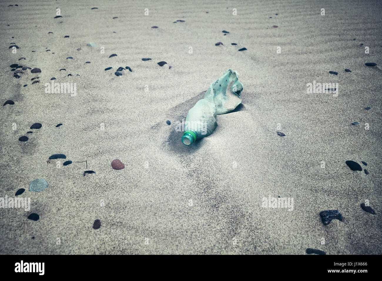 Color toned picture of an empty plastic bottle left on a beach, selective focus. - Stock Image