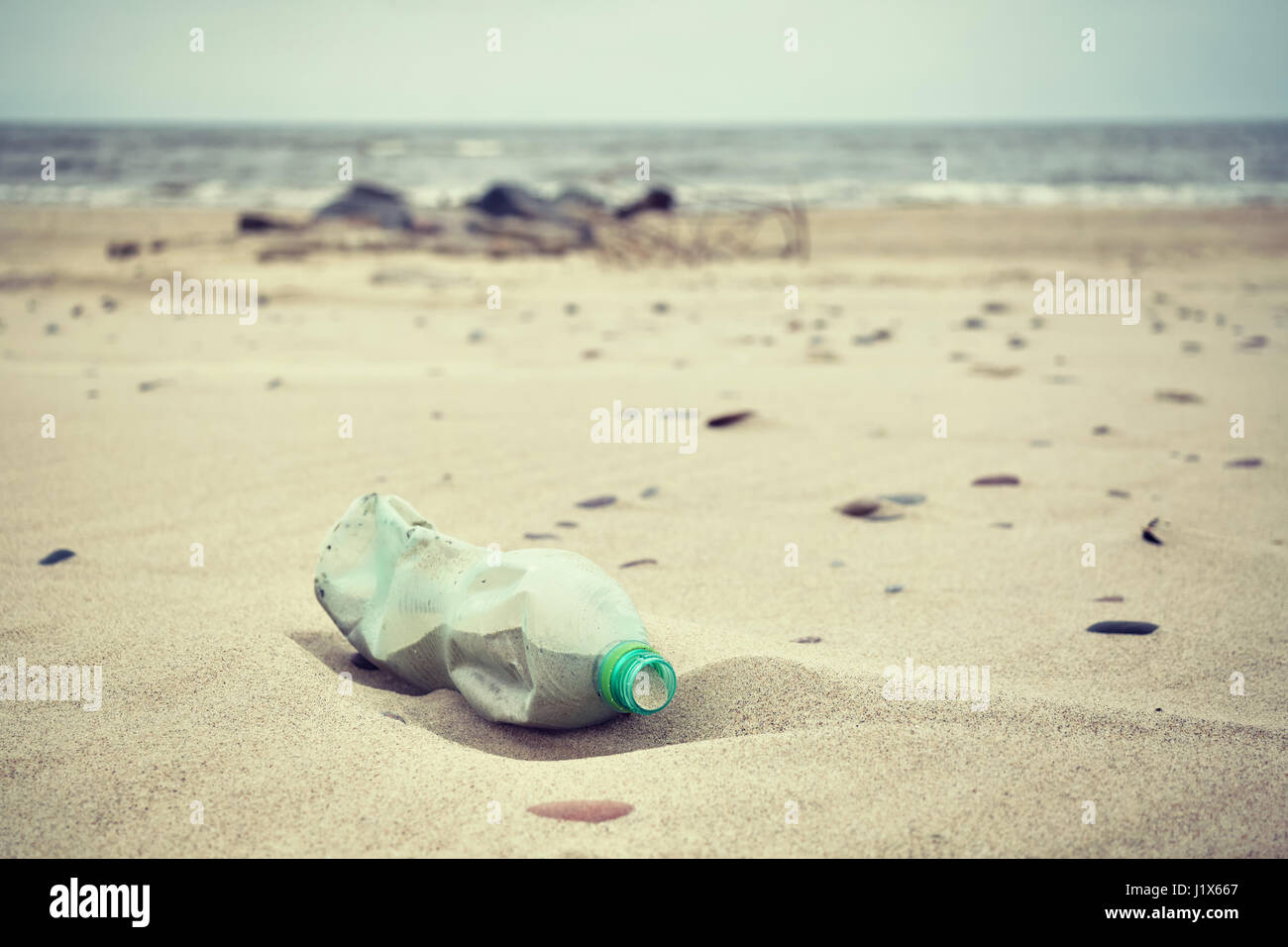 Retro stylized picture of an empty green plastic bottle left on a beach, selective focus, environmental pollution - Stock Image