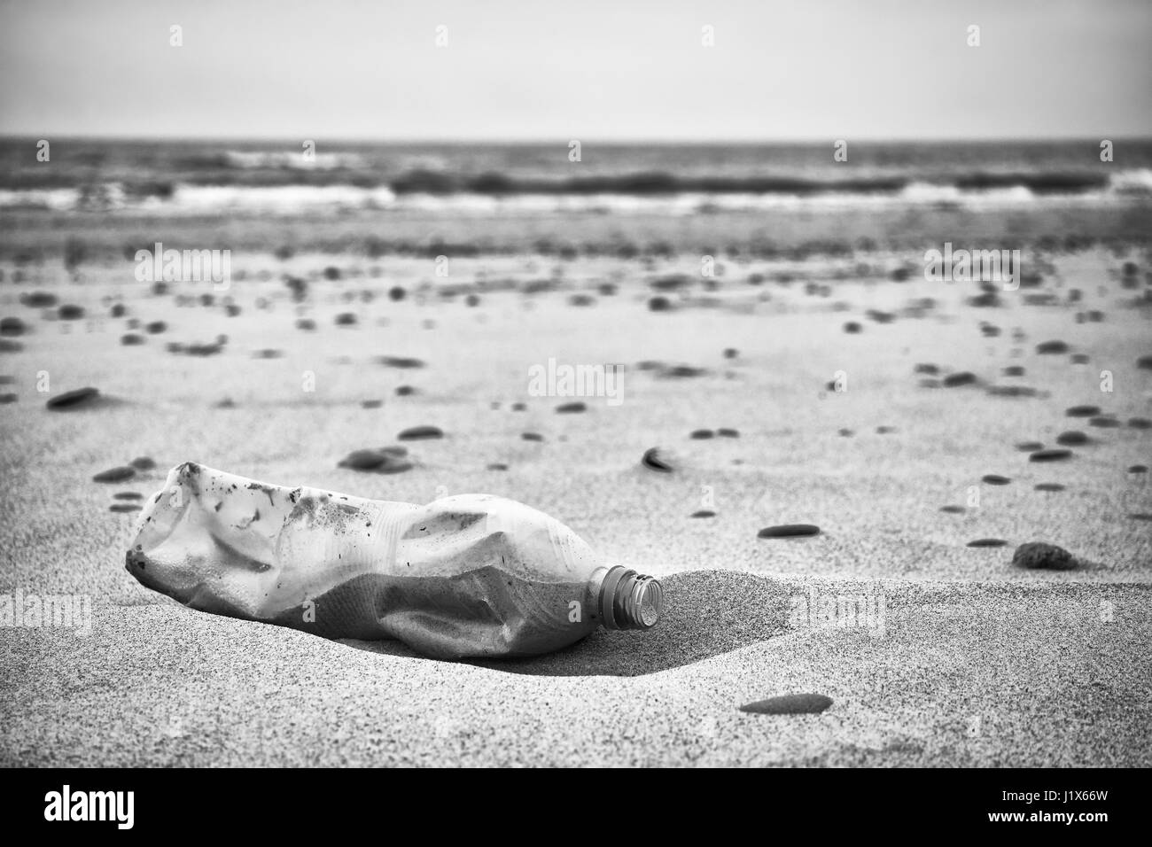 Black and white picture of an empty plastic bottle left on a beach, selective focus, environmental pollution concept - Stock Image