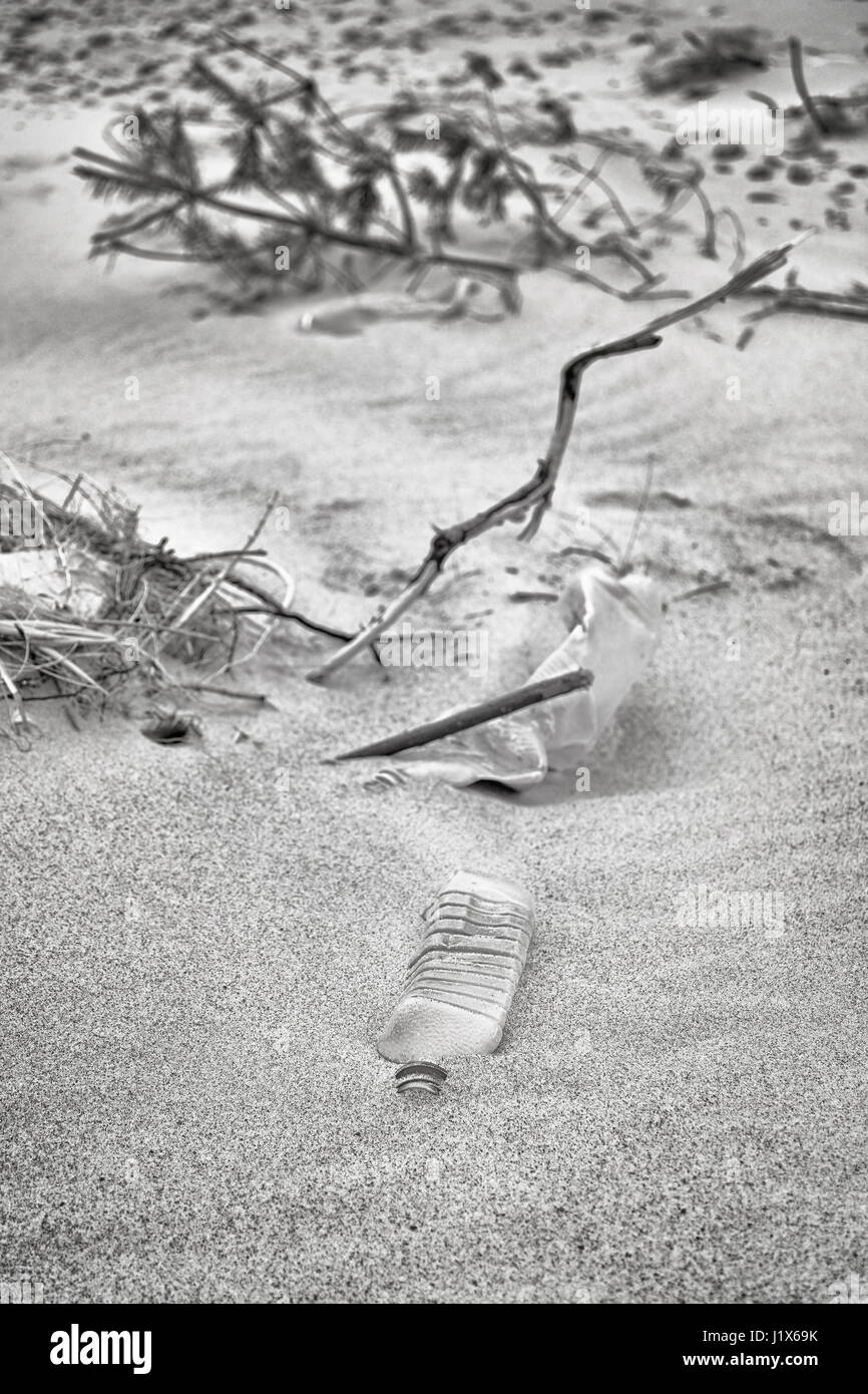 Black and white picture of plastic bottles left on a beach, selective focus, environmental pollution concept picture. - Stock Image