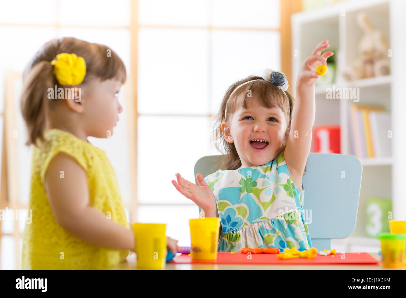 Little kids having fun together with colorful modeling clay at daycare. Creative kids molding at home. Children - Stock Image