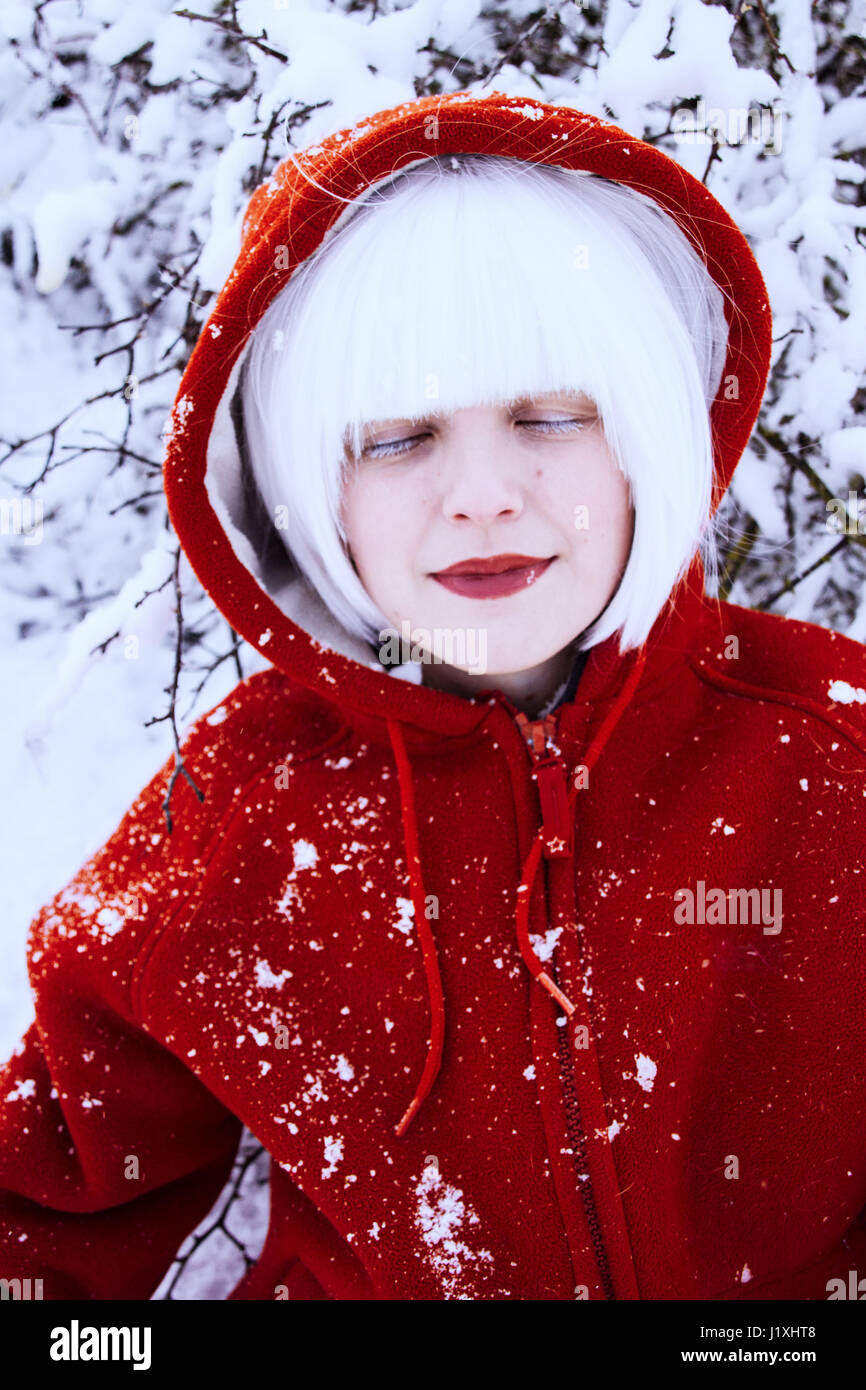 Young woman with red hood and white hair in winter - Stock Image