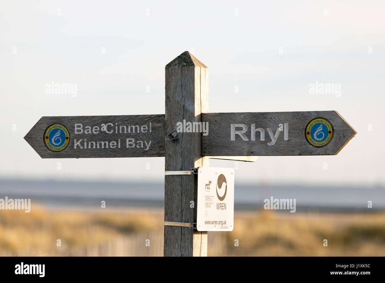 Wooden beach sign with the words Rhyl and Bae Cinmel Kinmel Bay on part of the Welsh Coastal Path at the seaside - Stock Image