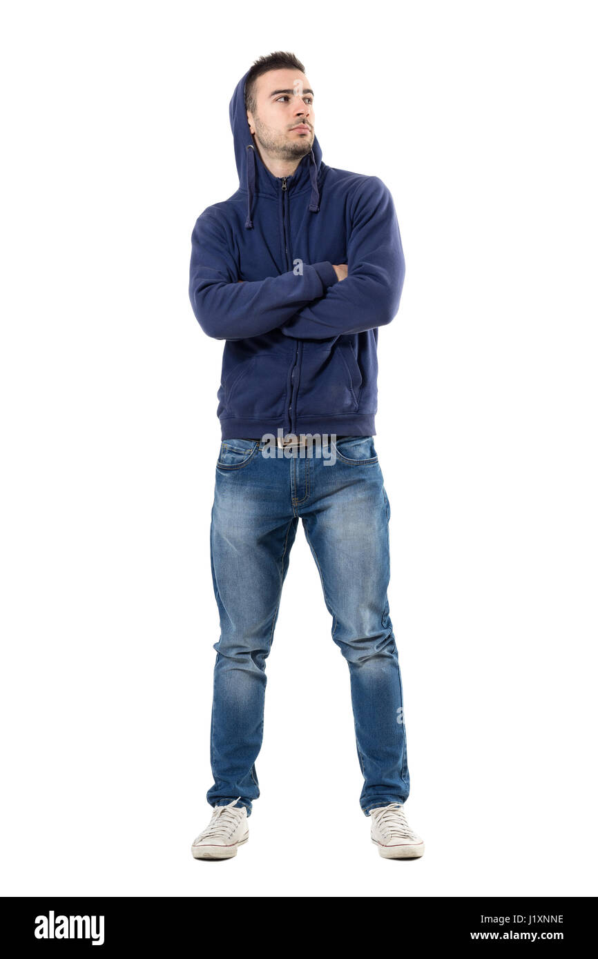 cc9da542 Tough confident young man with hoodie on head and crossed arms looking up.  Full body length portrait isolated over white studio background.