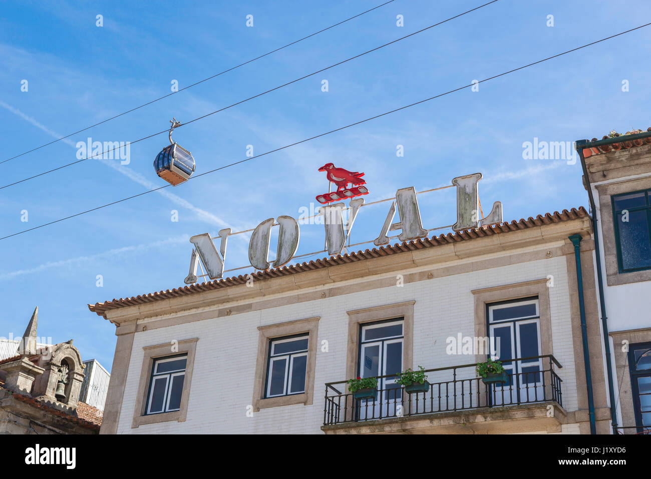 Porto Portugal Gaia, a cable car carrying tourists passes over a Noval Port sign in the waterfront Gaia district - Stock Image