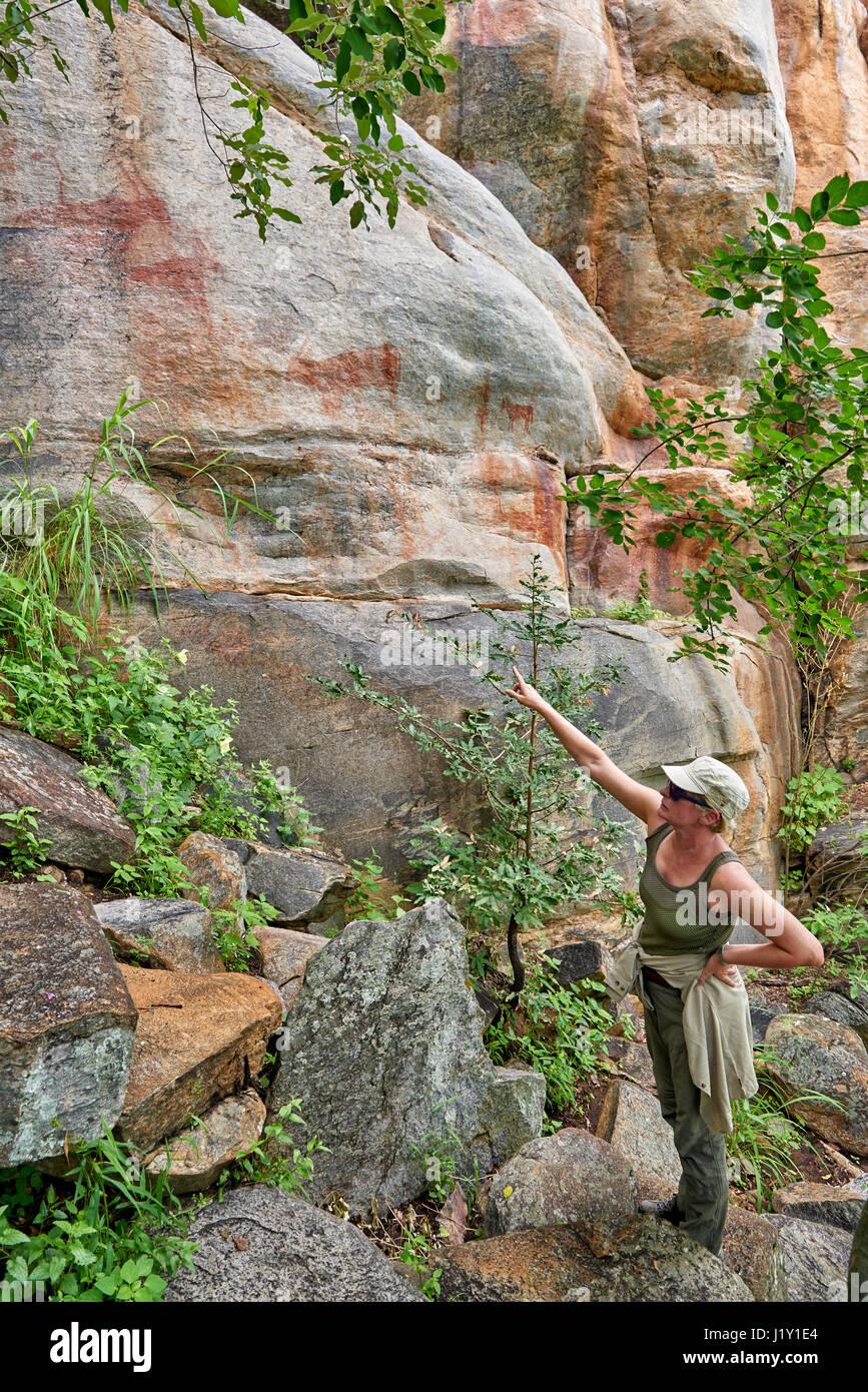 tourist looks on Rock art, ancient San paintings, Tsodilo Hills, Botswana, Africa - Stock Image