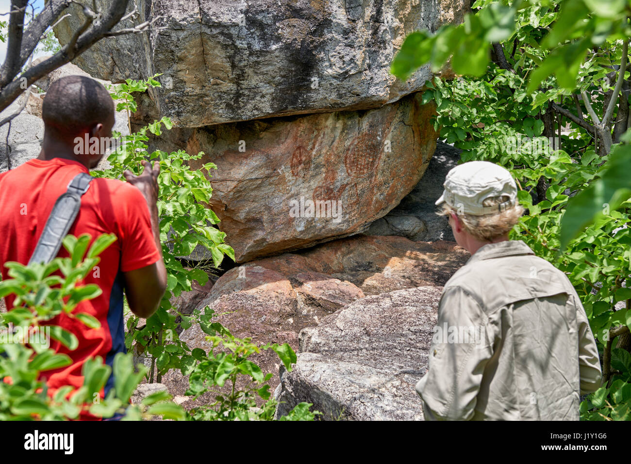 tourist and guide looking on Rock art, ancient San paintings, Tsodilo Hills, Botswana, Africa - Stock Image