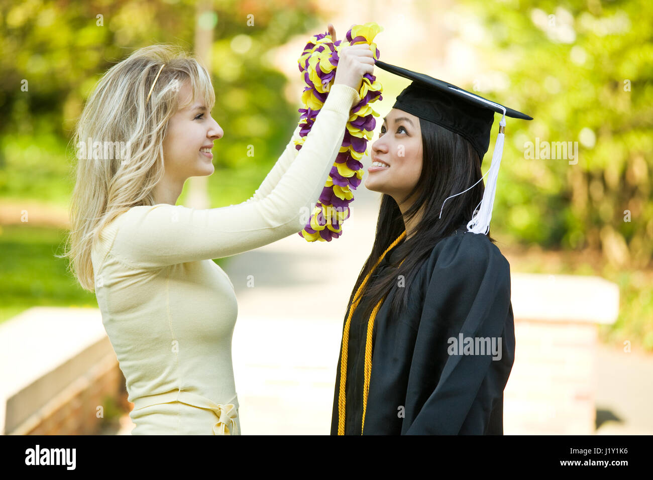A happy beautiful graduation girl being congratulated by her friend - Stock Image