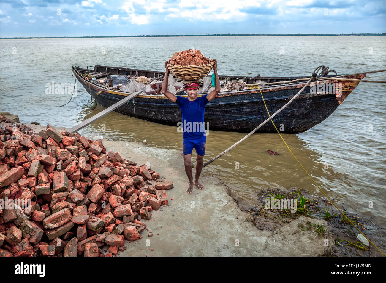 A worker transporting red bricks from a wooden boat onto the Rupnarayan riverbank in Tamluk, West Bengal, India. Stock Photo