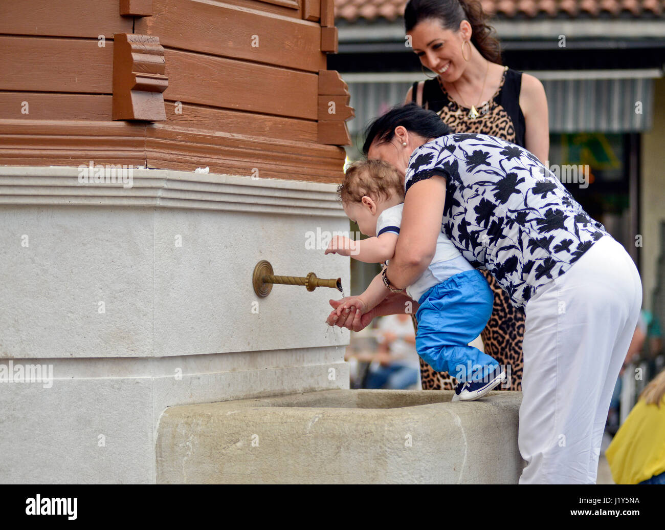 Grandmother cleaning her grandson in a water fountain. Bascarsija, Sarajevo - Stock Image