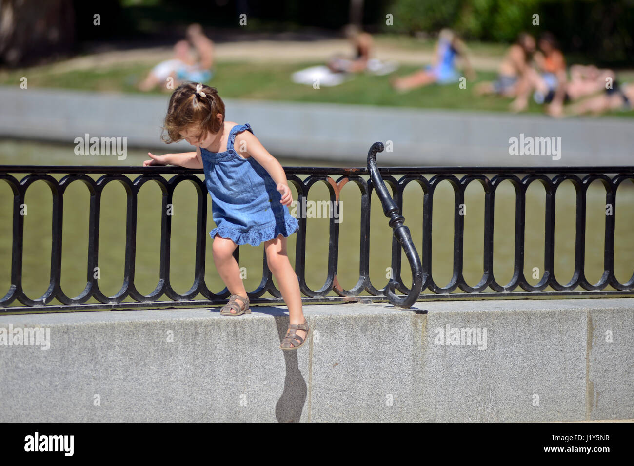 A little girl stepping down a fence. Parque del Retiro, Madrid, Spain - Stock Image