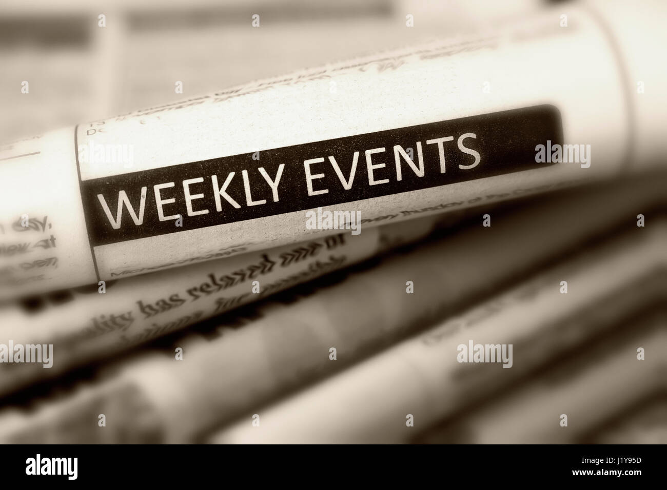 Headline Weekly events of one of newspaper in the pile of newspapers. Black and white. - Stock Image