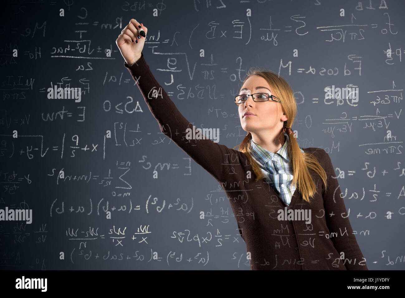 Schoolgirl work assignments in mathematics on transparent wall - Stock Image