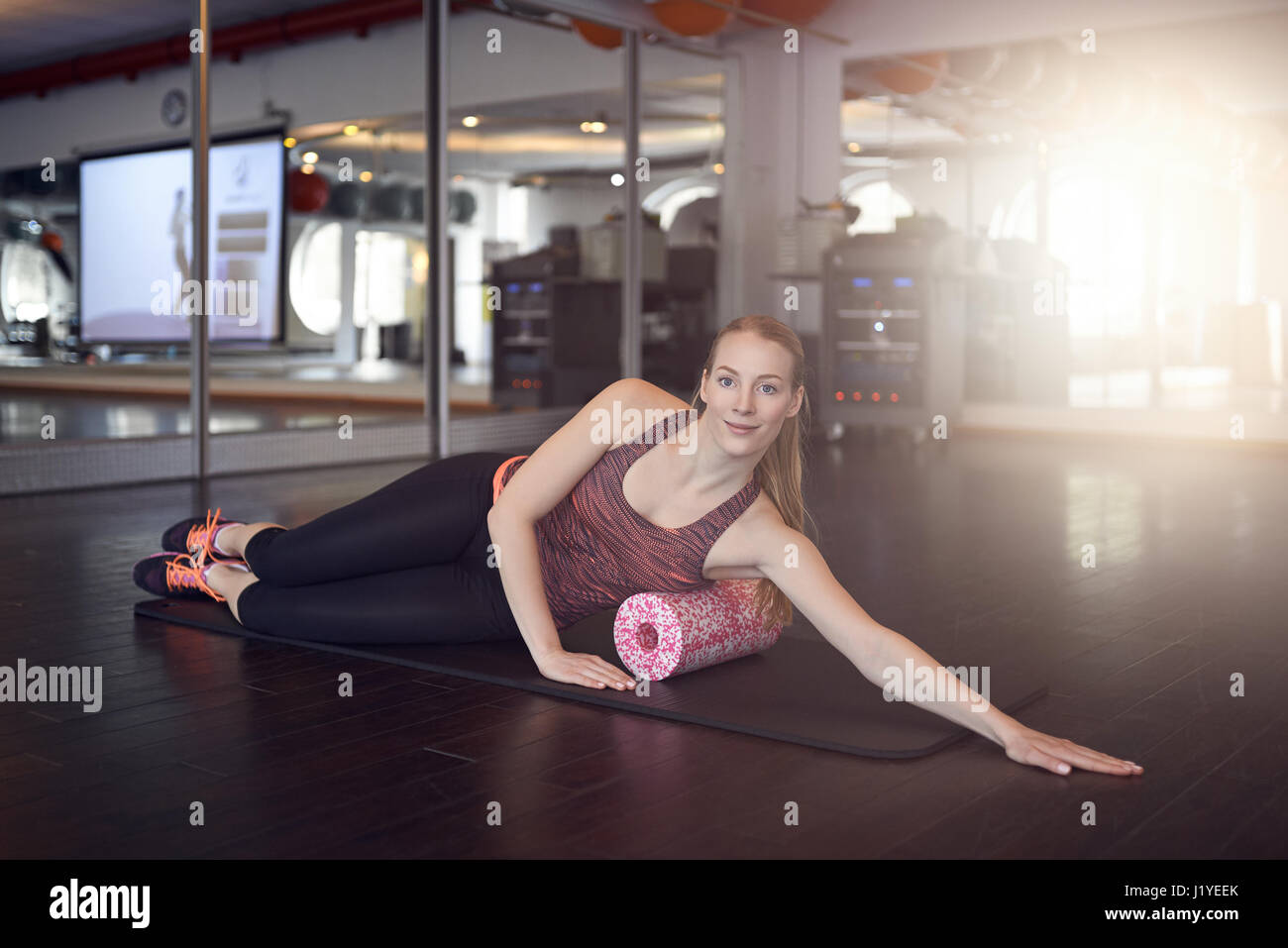 Woman in sleeveless shirt and black leggings in gym doing exercise with foam or fascia roll and looking at camera - Stock Image