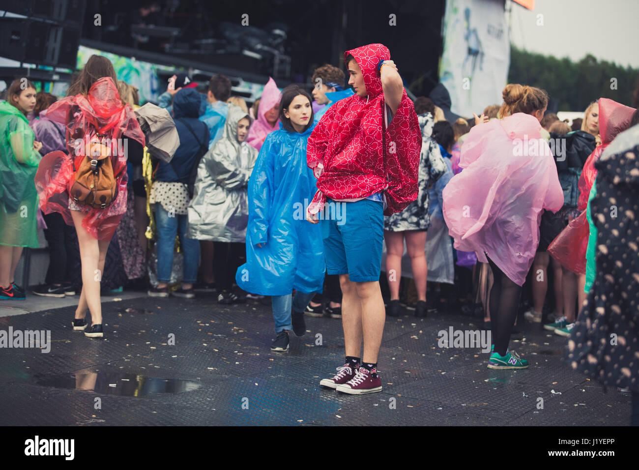 Festival-goers in plastic ponchos in rain at Open'er Festival in Poland. - Stock Image