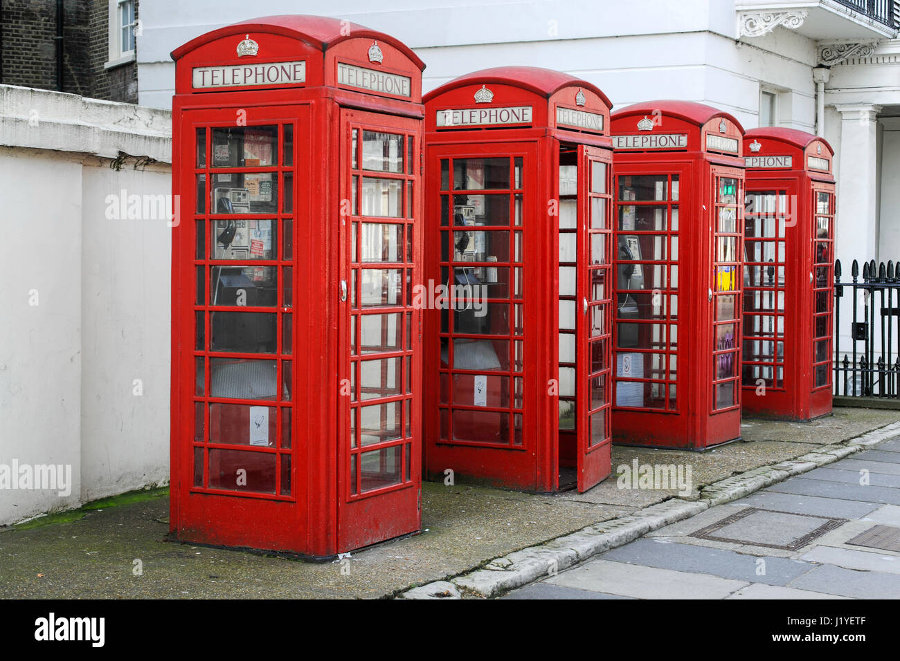 Four public red telephone boxes, or kiosks, in London - Stock Image