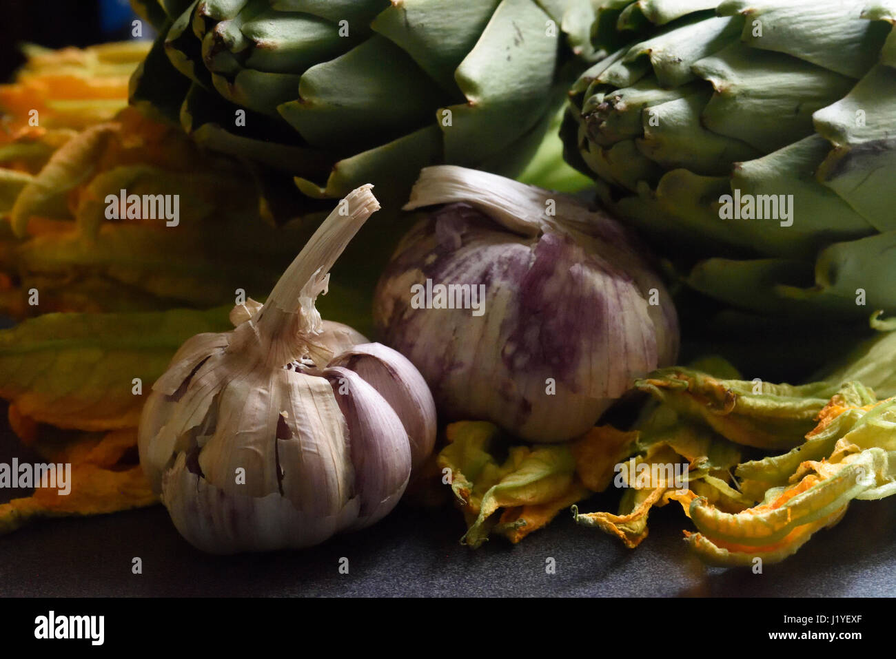 Mixed vegetables, featuring garlic and artichokes, in grainy moody lighting - Stock Image