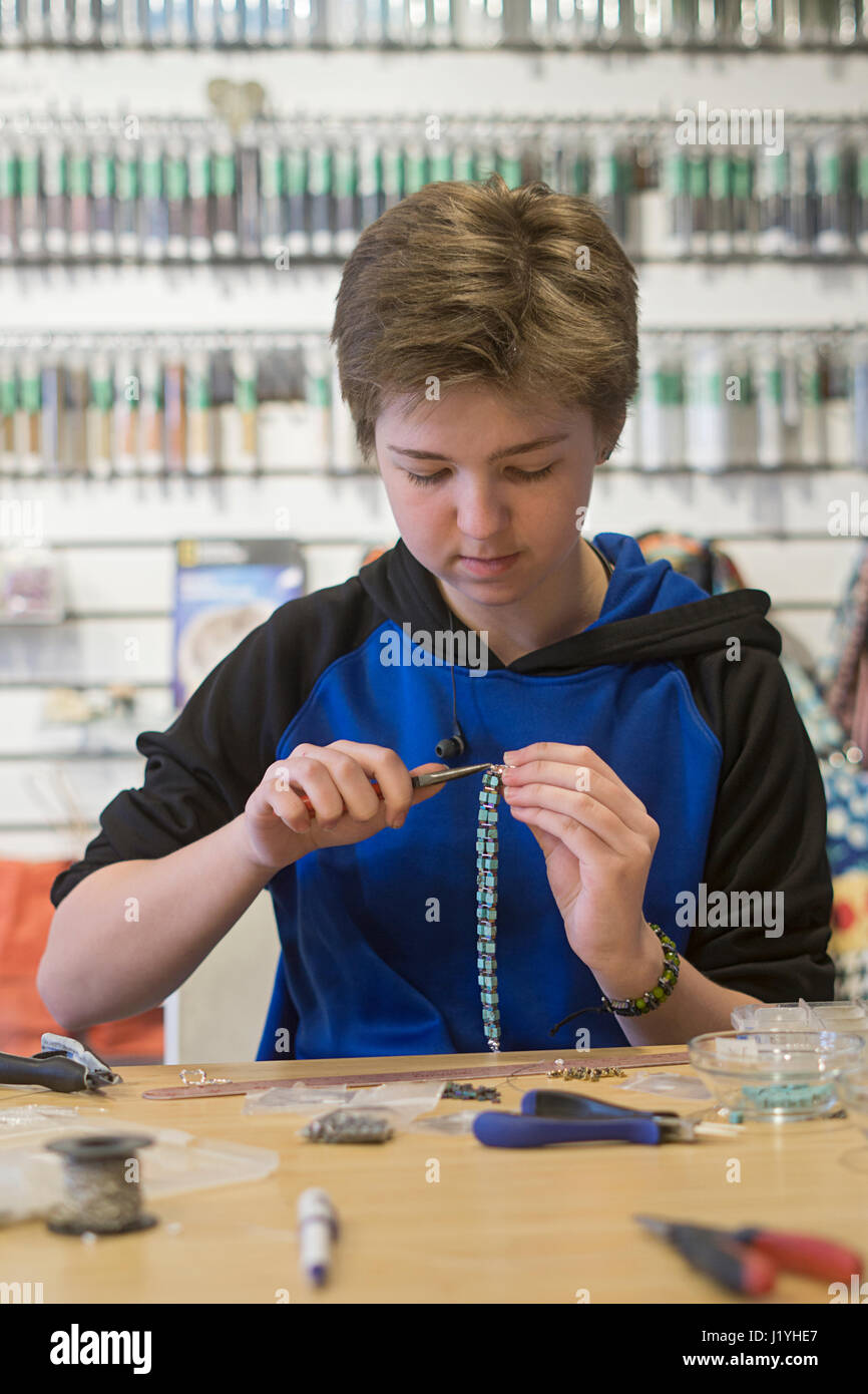 A teenage high school student working part time in her mother's jewelry shop. - Stock Image