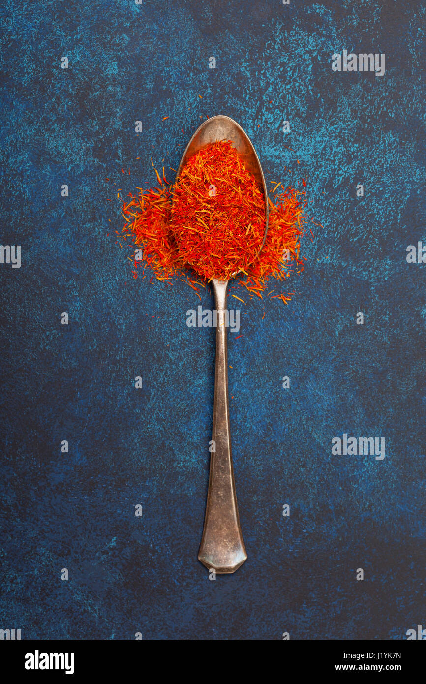 Saffron in an old silver spoon on a blue background. View from above. - Stock Image