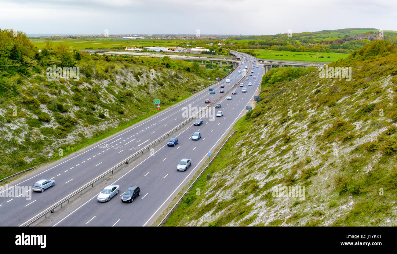 Country road. Cars on the A27 3 lane carriageway through a valley cut through hills in the British countryside in - Stock Image