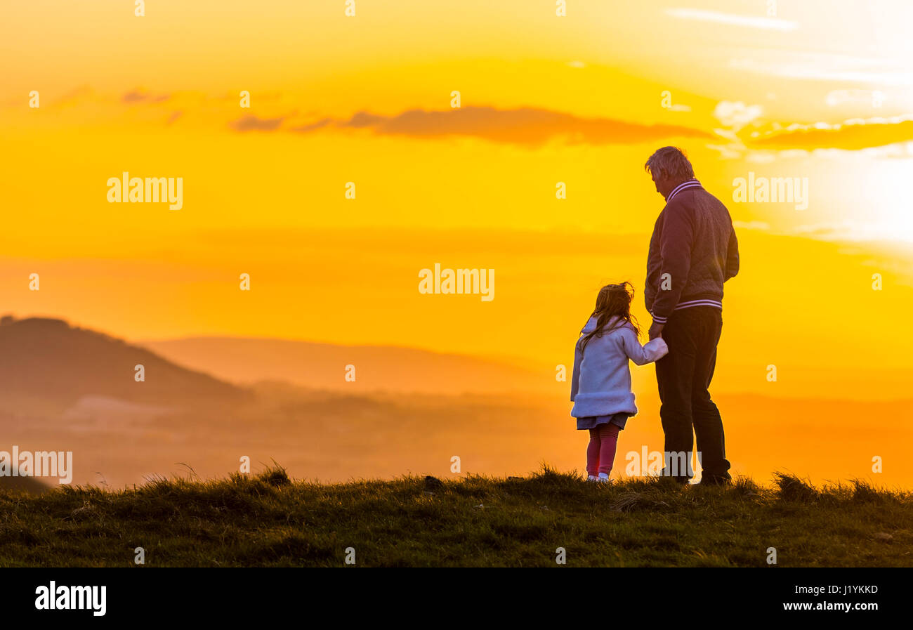 Father daughter relationship. Father and Daughter standing together holding hands on a hill, enjoying watching the - Stock Image