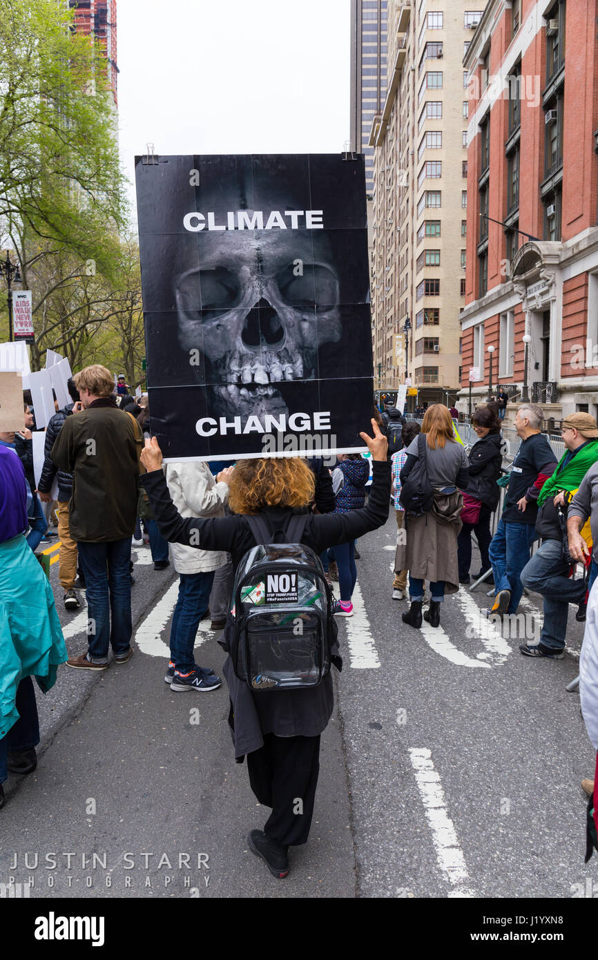 """New York, USA. 22nd April, 2017. An unidentified woman holds a sign that has a big skull and reads """"Climate Change"""" Stock Photo"""