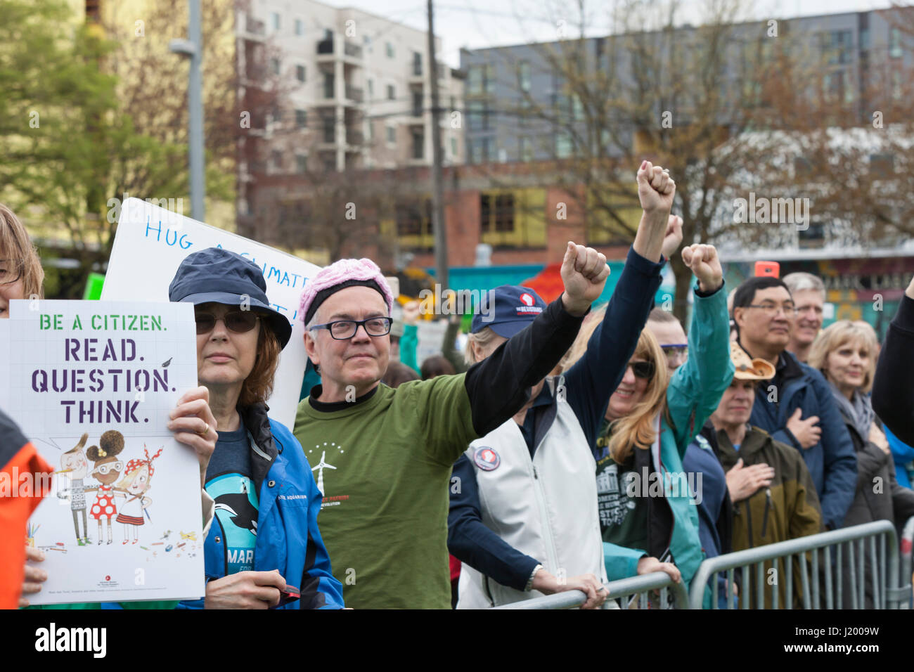 Seattle, Washington,USA. 22nd April, 2017. Protestors raise their fists during the national anthem at the rally Stock Photo